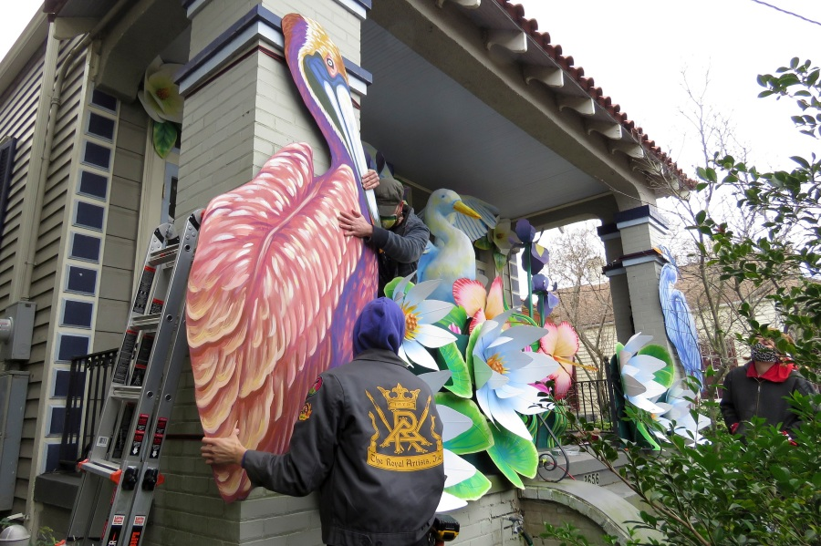 Parade float workers Travis Keene, left, and Joey Mercer position a pelican while fellow crew member Chelsea Kamm, right, looks on while decorating a house in New Orleans on Jan. 8, 2021. All around the city, thousands of houses are being decorated as floats because the coronavirus pandemic has canceled parades that usually take place on Mardi Gras. (AP Photo/Janet McConnaughey)
