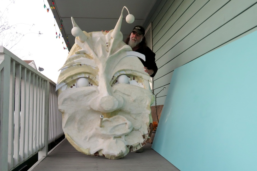 "Thom Karamus shows his paper mache head of the hookah-smoking caterpillar from ""Alice in Wonderland,"" on Jan. 14, 2021, in New Orleans. All around the city, thousands of houses are being decorated as floats because the coronavirus pandemic has canceled parades that usually take place on Mardi Gras. (AP Photo/Janet McConnaughey)"