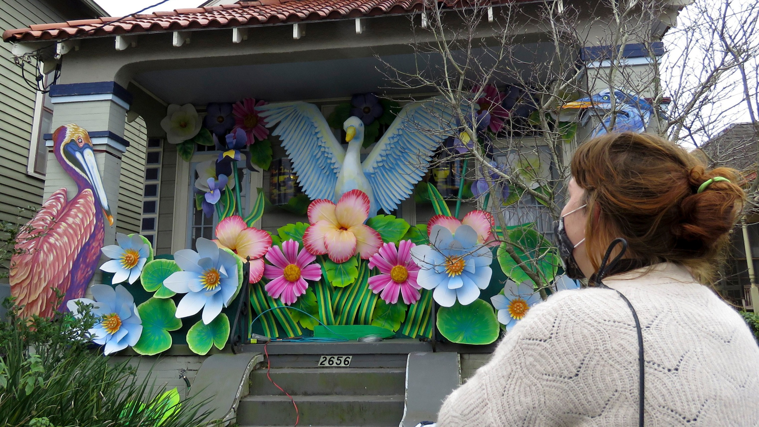 Designer Caroline Thomas looks at a house decorated like a parade float in New Orleans on Friday, Jan. 8, 2021. All around the city, thousands of houses are being decorated as floats because the coronavirus pandemic has canceled parades that usually take place on Mardi Gras. (AP Photo/Janet McConnaughey)