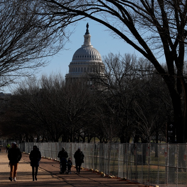 People stroll past a section of the National Mall by the Capitol where workers were still dismantling inauguration installations, after most downtown streets and public spaces had reopened to the public, on Saturday, Jan. 23, 2021 in Washington. (AP Photo/Rebecca Blackwell)