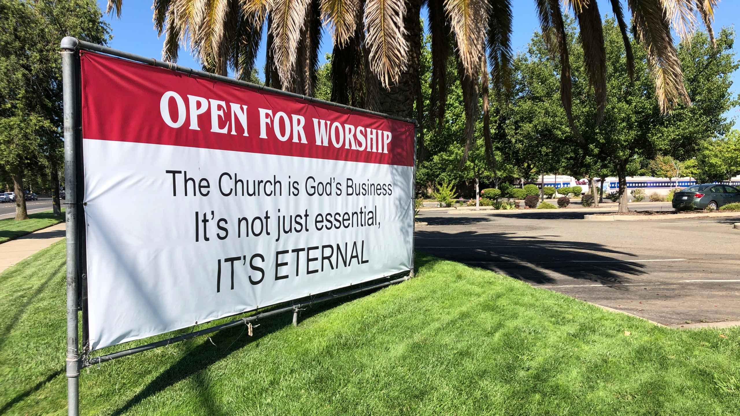 "This July 9, 2020 file photo shows a banner reading: ""Open for Worship, The Church is God's Business It's not just essential, It's Eternal,"" posted outside the Crossroads Community Church in Yuba City, Calif. (AP Photo/Adam Beam)"