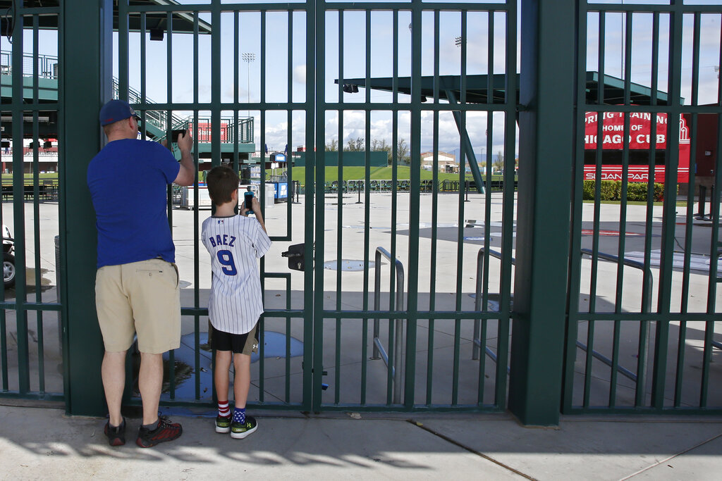 Cubs fans take photos through the locked gates at Sloan Park, the spring training site of the Chicago Cubs, in Mesa, Ariz., after Major League Baseball suspended the rest of its spring training game schedule because of the coronavirus outbreak, in this Friday, March 13, 2020, file photo. (AP Photo/Sue Ogrocki, File)