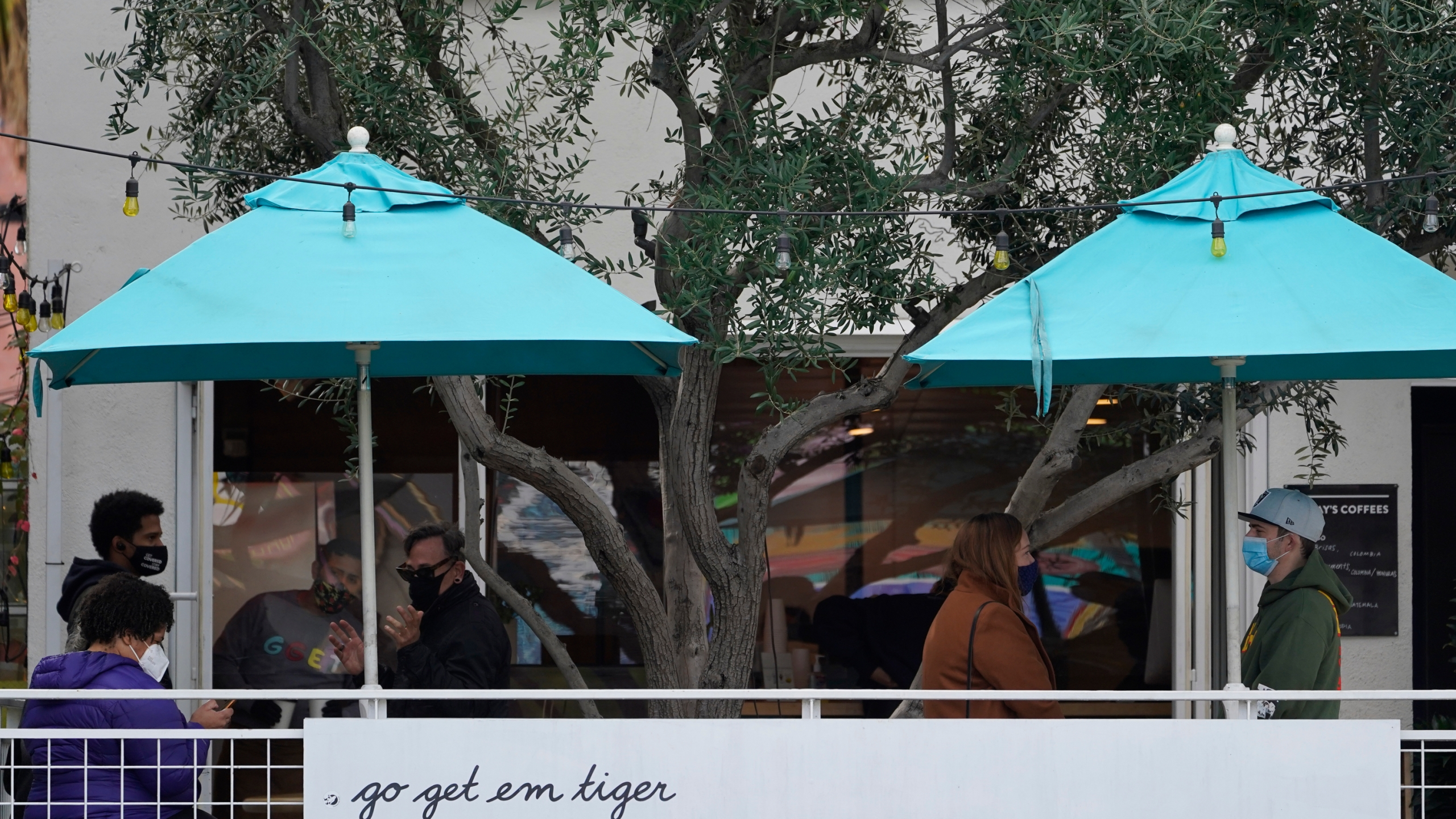 "People wear masks as they wait outdoors for takeaway coffee and eats at the ""go get em tiger"" coffee bar on Hollywood Blvd., in Los Angeles Monday, Jan. 25, 2021. (AP Photo/Damian Dovarganes)"