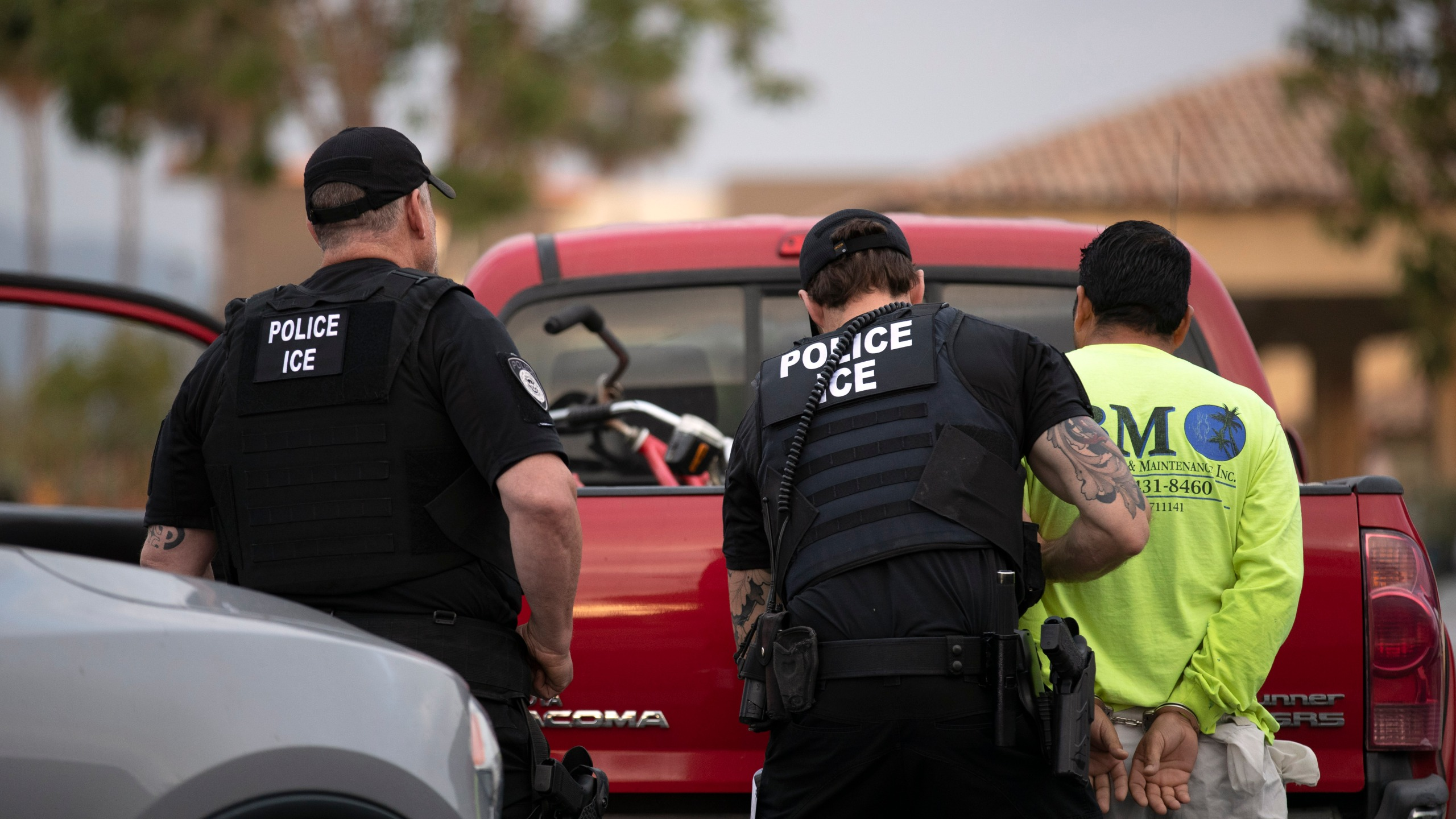 U.S. Immigration and Customs Enforcement (ICE) officers detain a man during an operation in Escondido, Calif., on July 8, 2019. (Gregory Bull / Associated Press)