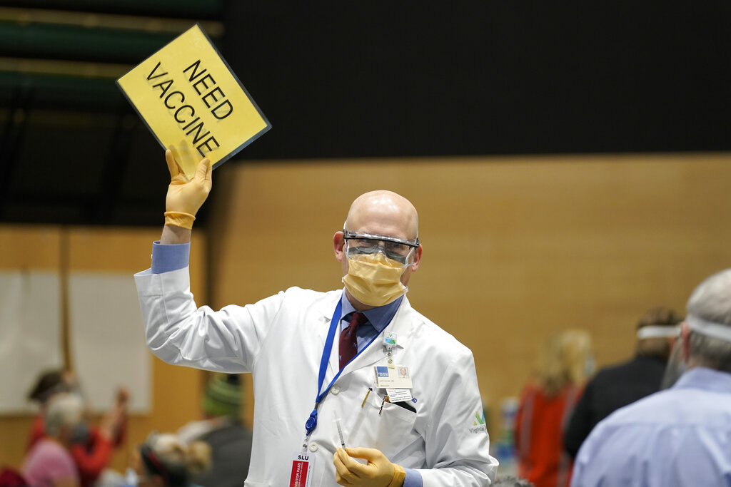 "In this Jan. 24, 2021, file photo, Dr. John Corman, the chief clinical officer for Virginia Mason Franciscan Health, holds a sign that reads ""Need Vaccine"" to signal workers to bring him more doses of the Pfizer vaccine for COVID-19 as he works at a one-day vaccination clinic set up in an Amazon.com facility in Seattle. (AP Photo/Ted S. Warren, File)"