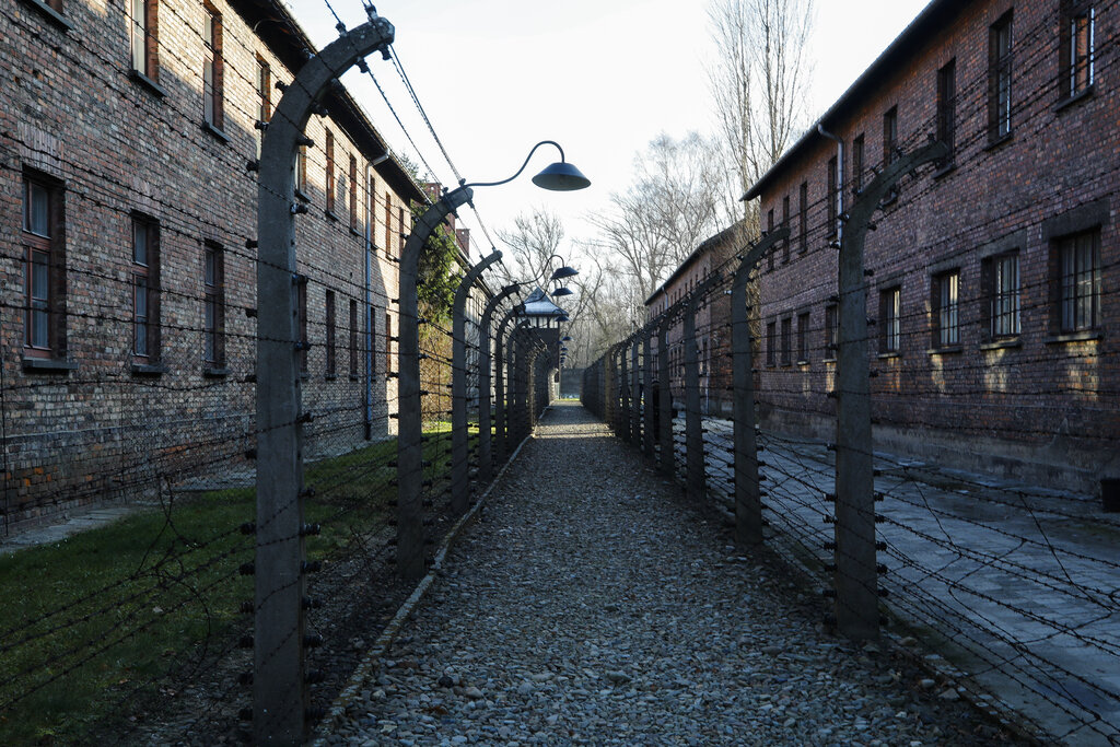 A pathway leading to an observation and security tower between what were electric barbed wire fences inside the former Nazi death camp of Auschwitz I in Oswiecim, Poland, Sunday, Dec. 8, 2019. (AP Photo/Markus Schreiber)
