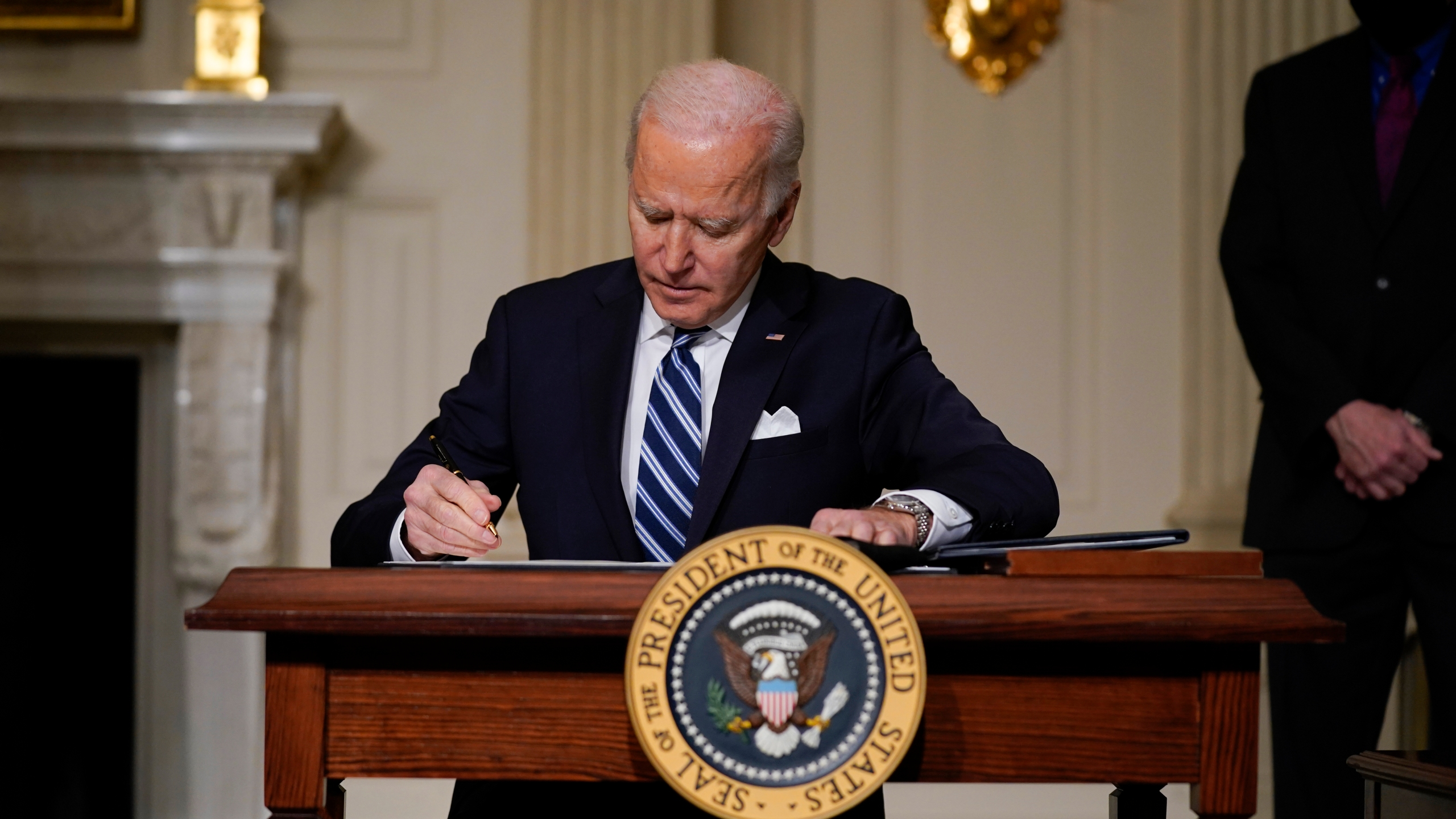 President Joe Biden signs an executive order on climate change in the State Dining Room of the White House on Jan. 27, 2021. (Evan Vucci / Associated Press)