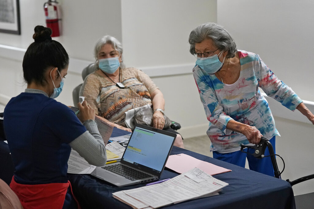 Mitzi Hansrote, right, 86, and Deanna Sutton, center, 83, check in before receiving the COVID-19 vaccine, Thursday, Jan. 21, 2021, at the Isles of Vero Beach assisted and independent senior living community in Vero Beach, Fla. (AP Photo/Wilfredo Lee)