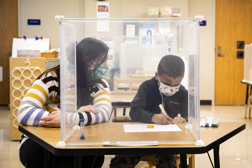 In this Jan. 11, 2021 file photo, pre-kindergarten teacher Sarah McCarthy works with a student at Dawes Elementary in Chicago. (Ashlee Rezin Garcia/Chicago Sun-Times via AP, Pool, File)