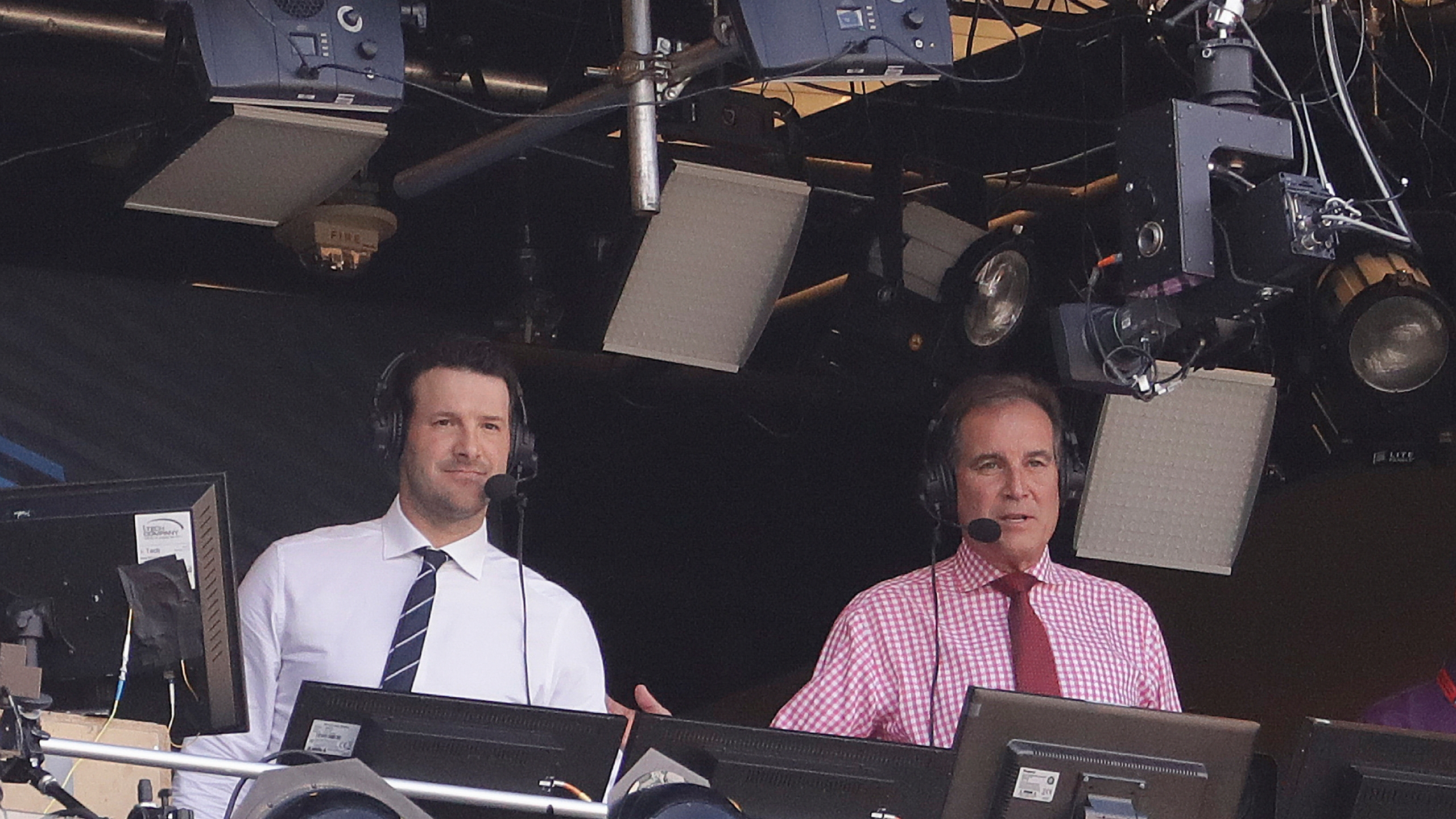 In this Sept. 24, 2017, file photo, Tony Romo and Jim Nantz work in the broadcast booth before an NFL football game between the Green Bay Packers and the Cincinnati Bengals in Green Bay, Wis. Nantz and Romo were inseparable when CBS broadcast the Super Bowl two years ago. Next week, they won't see each other until they are in the broadcast booth a couple hours prior to kickoff. Keeping announcers separated until game day has been standard practice this season due to the Coronavirus pandemic. (AP Photo/Morry Gash, File)