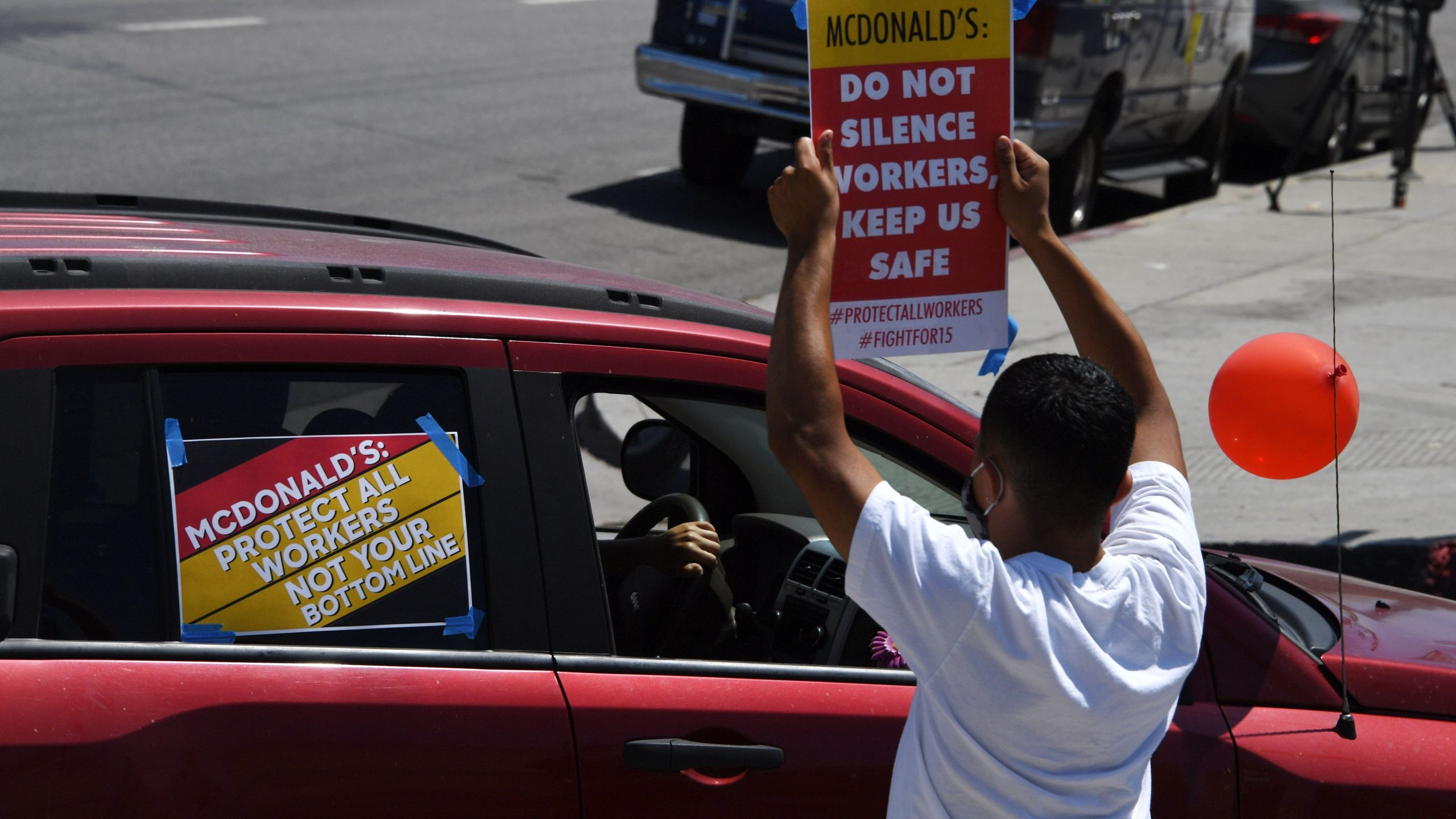 McDonald's workers and their supporters hold signs at a rally to protest what they allege is McDonald's attempts to silence a worker who spoke out about unsafe conditions amid the COVID-19 pandemic, August 7, 2020 outside a McDonald's in Los Angeles. (ROBYN BECK/AFP via Getty Images)