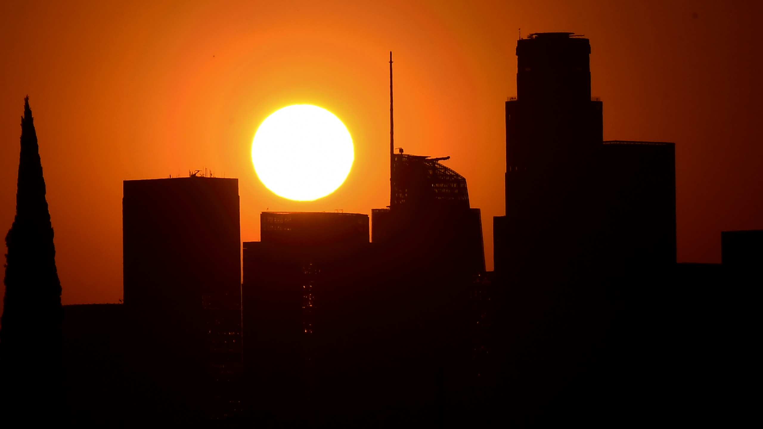 The sun sets behind highrise buildings in downtown Los Angeles on Sept. 30, 2020. (Frederic J. Brown / AFP / Getty Images)