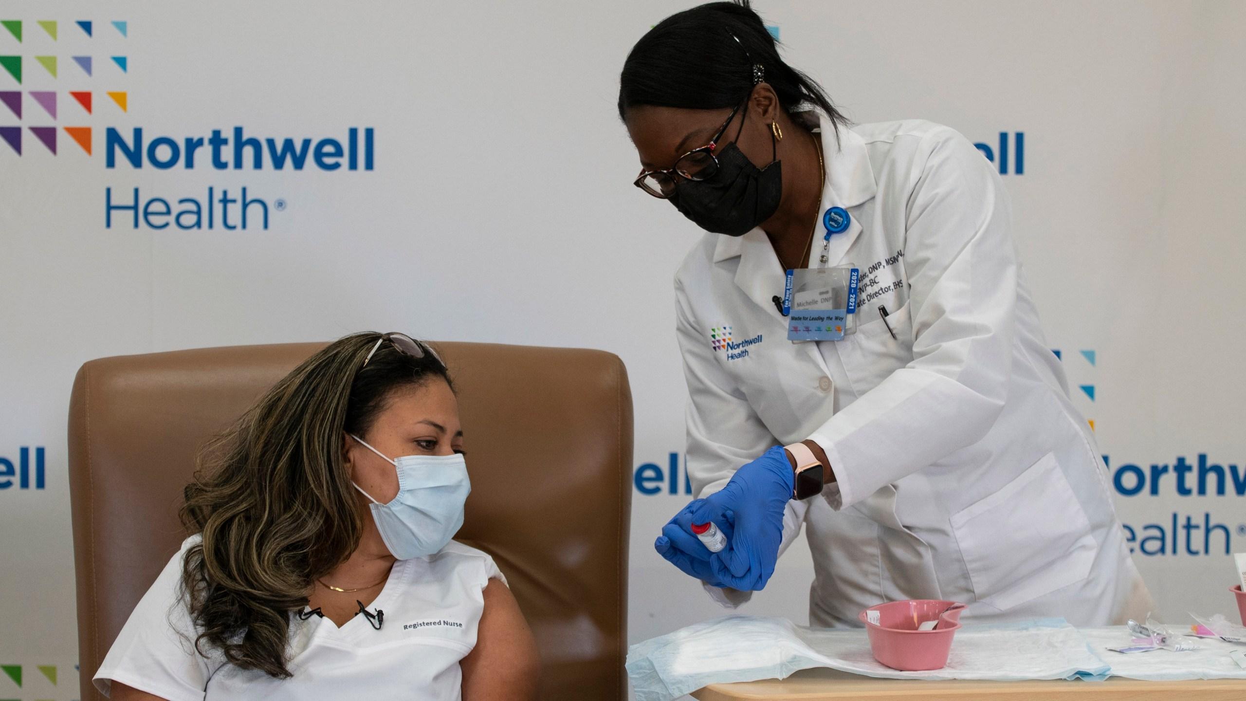 Michelle Chester (R), DNP, director, employee health services, Northwell shows the Moderna coronavirus disease (COVID-19) vaccine to Arlene Ramirez, RN, director, patient care, ED, Long Island Jewish Valley Stream, at Northwell Health's Long Island Jewish Valley Stream hospital in New York City, December 21, 2020. (Photo by Eduardo MUNOZ ALVAREZ / POOL / AFP) (Photo by EDUARDO MUNOZ ALVAREZ/POOL/AFP via Getty Images)