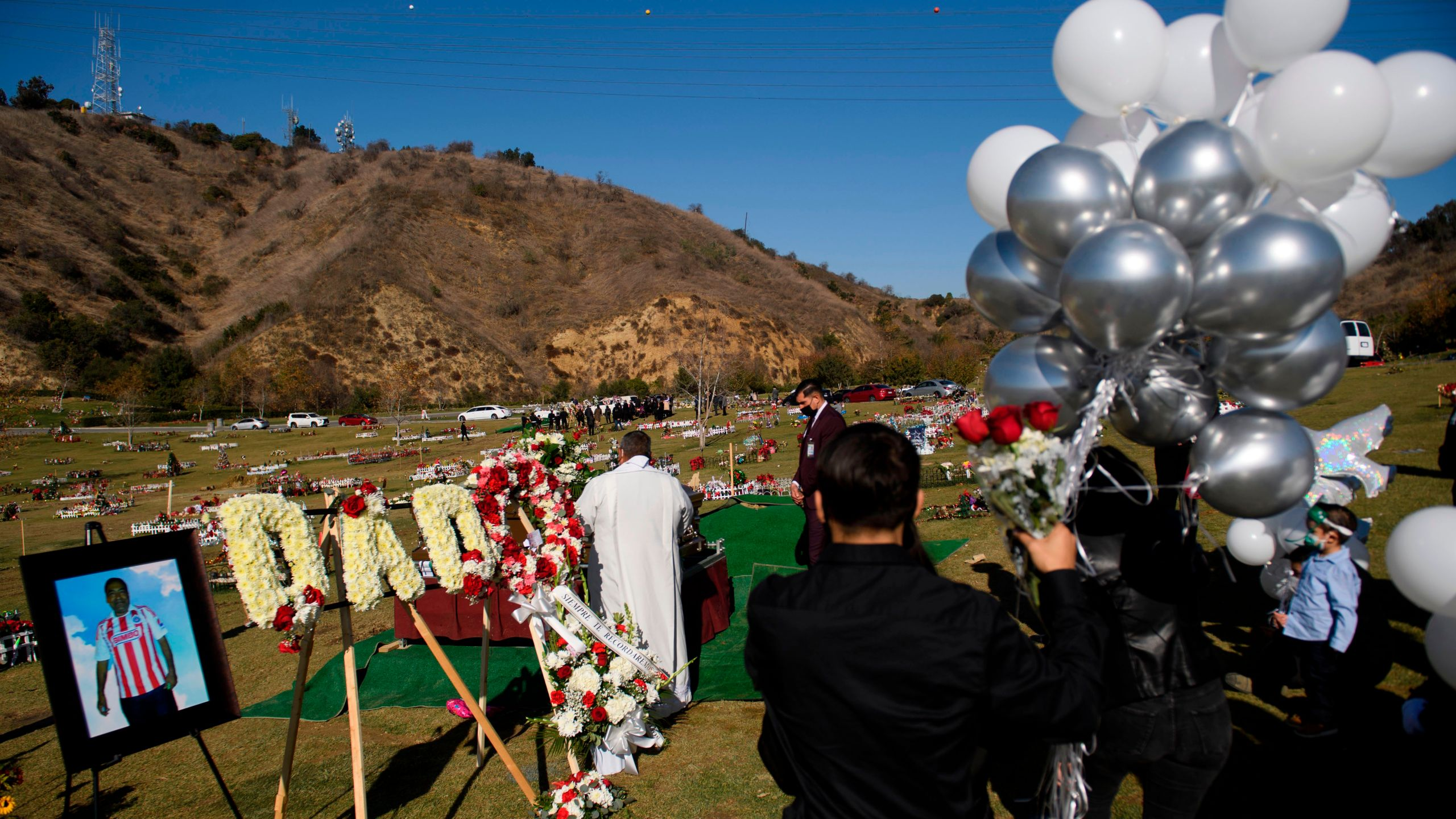 Family members mourn during a burial service for Gilberto Arreguin Camacho, 58, following his death due to COVID-19, at a cemetery on New Year's Eve, Dec. 31, 2020 in Whittier. (PATRICK T. FALLON/AFP via Getty Images)