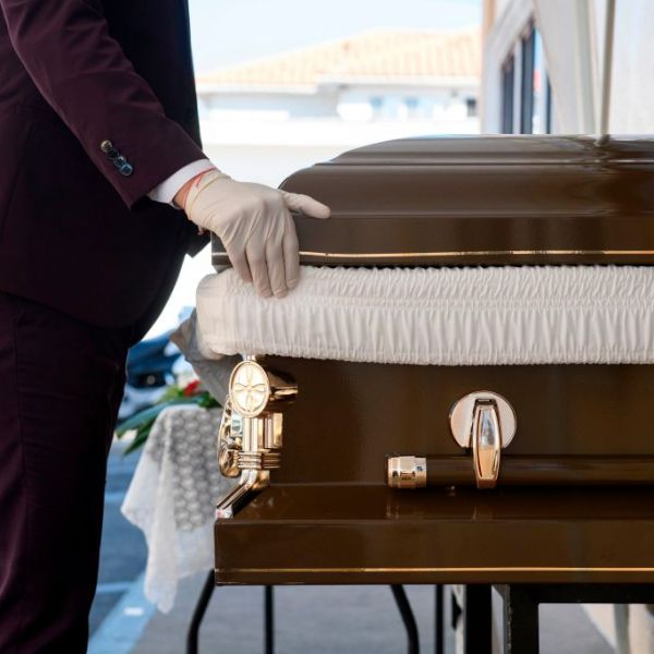 Funeral director Steven Correa wears gloves as he moves the casket of Gilberto Arreguin Camacho, 58, in preparation for burial following his death due to COVID-19 at Continental Funeral Home on New Year's Eve, Dec. 31, 2020 in East Los Angeles. (PATRICK T. FALLON/AFP via Getty Images)