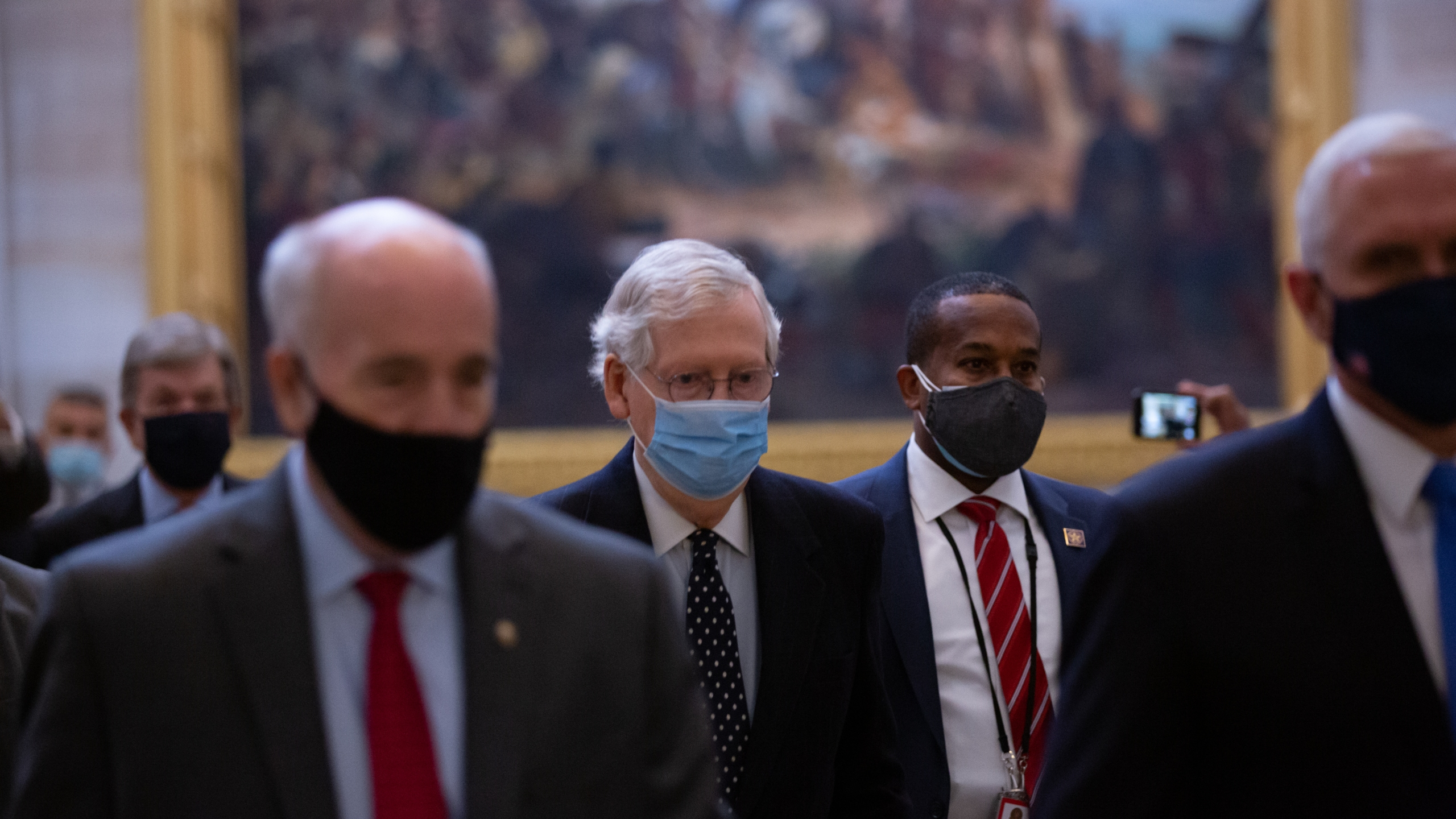 Senate Majority Leader Mitch McConnell, center, walks through the Rotunda headed to the House Chamber at the U.S. Capitol on Jan. 6, 2021. (Cheriss May / Getty Images)