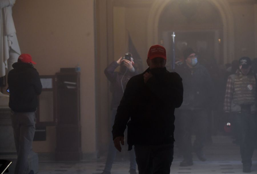 Supporters of President Donald Trump enter the US Capitol as tear gas fills the corridor on January 6, 2021, in Washington, DC. (Saul LOEB / AFP) (Photo by SAUL LOEB/AFP via Getty Images)