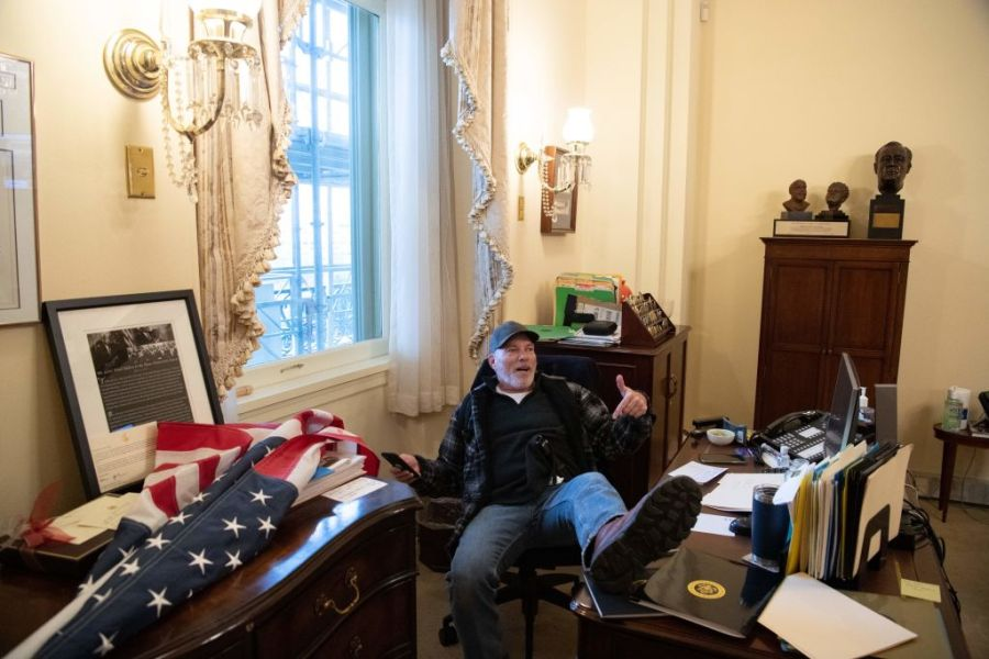 A supporter of President Donald Trump sits inside the office of US Speaker of the House Nancy Pelosi as he protest inside the US Capitol in Washington, DC, January 6, 2021. (SAUL LOEB/AFP via Getty Images)
