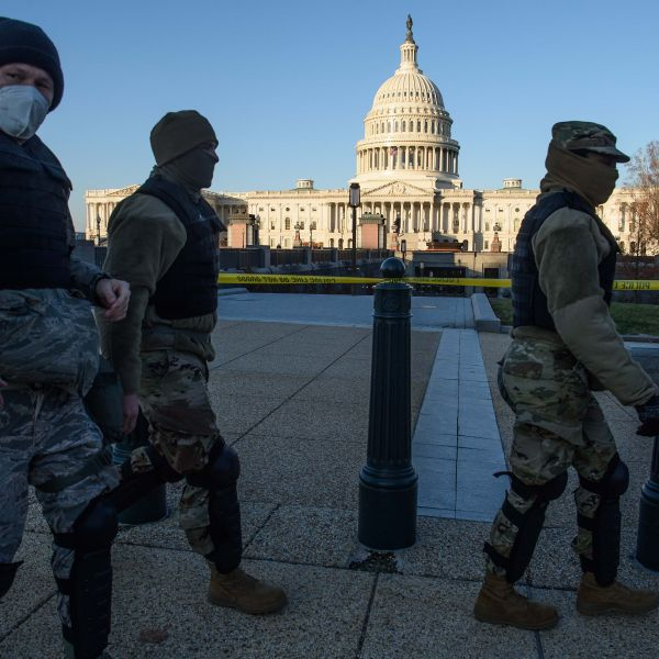 Members of the D.C. National Guard walk past the U.S. Capitol in Washington, D.C., on Jan. 7, 2020, one day after supporters of outgoing President Donald Trump stormed the building. (NICHOLAS KAMM/AFP via Getty Images)