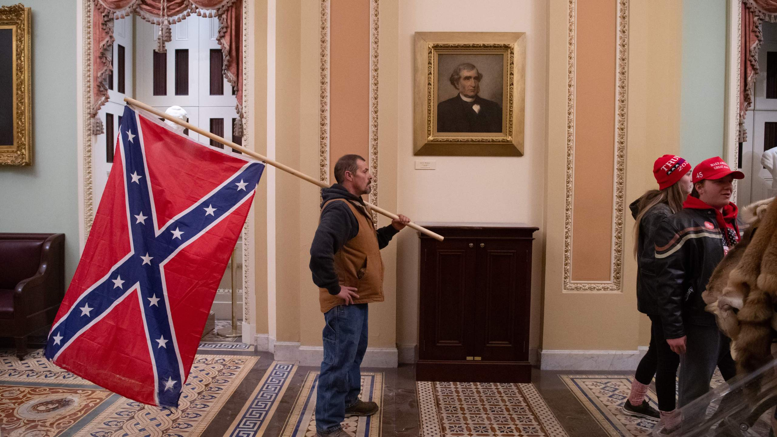 A supporter of Donald Trump holds a Confederate flag outside the Senate Chamber during a protest after breaching the US Capitol in Washington, D.C., Jan. 6, 2021. (SAUL LOEB/AFP via Getty Images)