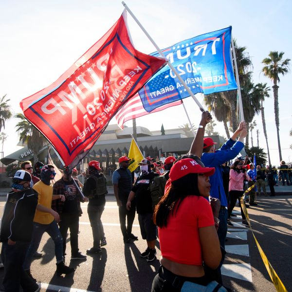"""People hold flags during a """"Patriot March"""" demonstration in support of Donald Trump, separated from counter-protesters by a police skirmish line on Jan. 9, 2021 in the Pacific Beach neighborhood of San Diego. (PATRICK T. FALLON/AFP via Getty Images)"""