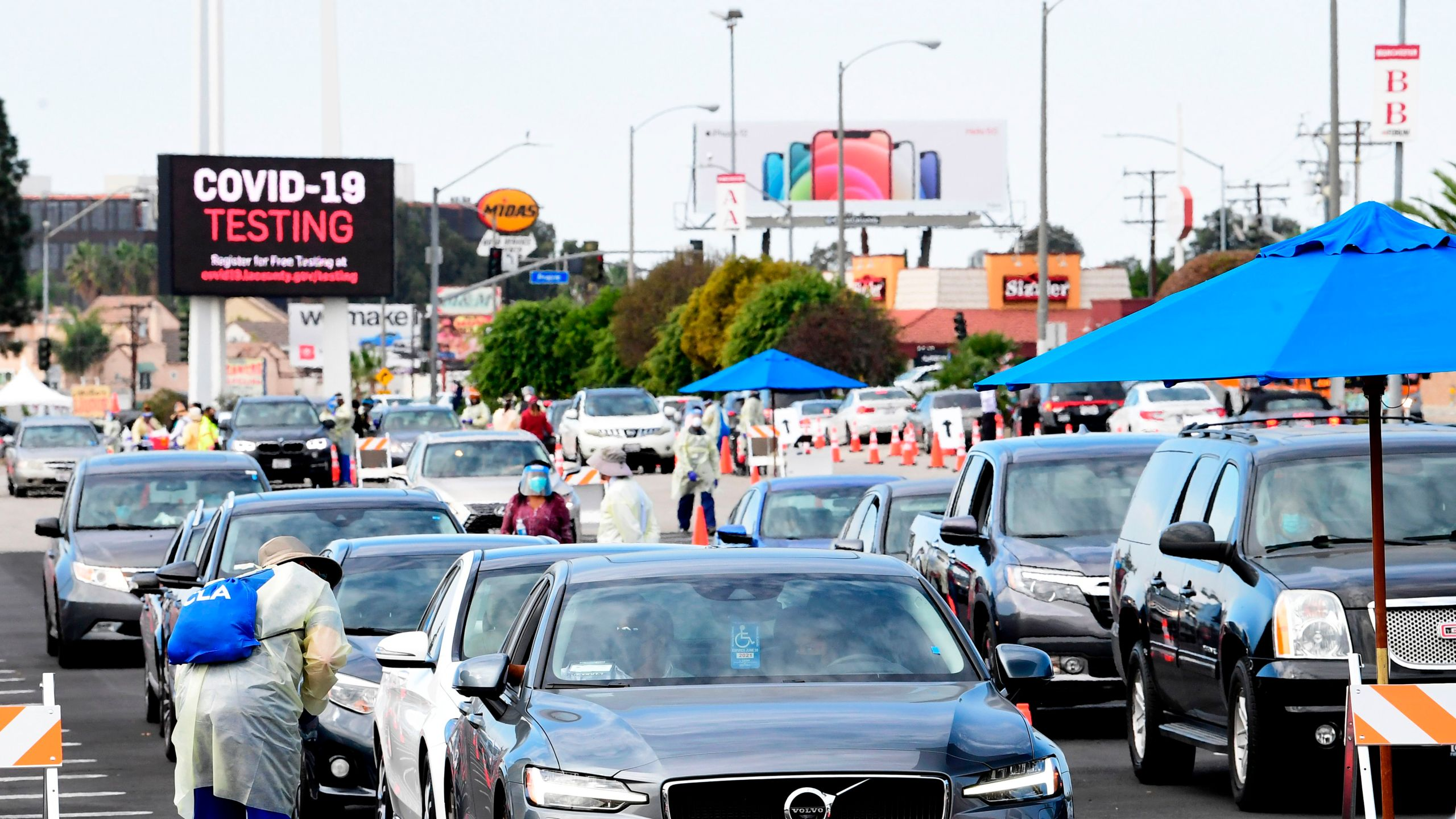 People pull up in their vehicles for COVID-19 vaccines in the parking lot of The Forum in Inglewood on Jan. 19, 2021. (FREDERIC J. BROWN/AFP via Getty Images)