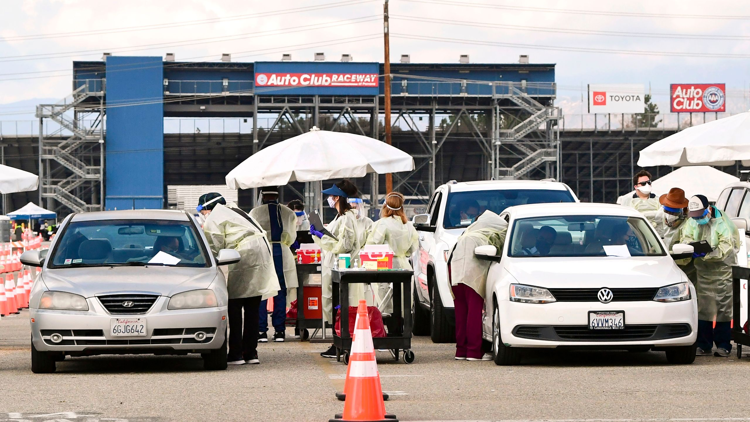 Health care personel dressed in personal protective gear help inoculate people arriving to receive COVID-19 vaccines at the Fairplex in Pomona on Jan. 22, 2021. (Frederic J. Brown / AFP / Getty Images)