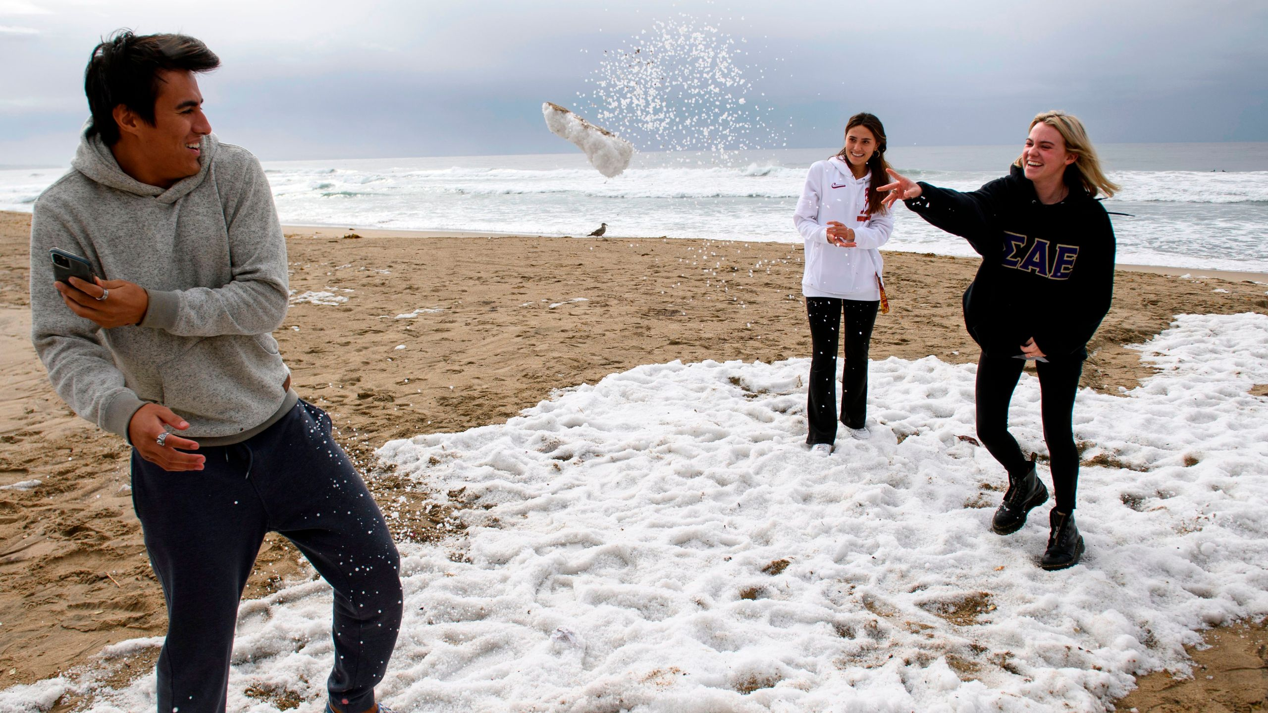MacKenzie Hill, (R) throws a snowball at Eddie Donovan (L) with Destiny Donovan (C, rear) as they play with hail on the beach following winter storms that blanketed the region with rain, snow, and hail, on Jan. 29, 2021 in Manhattan Beach, Calif. (Patrick T. FALLON / AFP via Getty Images)