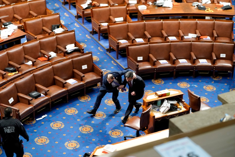 Members of Congress run for cover as protesters try to enter the House Chamber during a joint session of Congress on January 06, 2021 in Washington, DC. (Drew Angerer/Getty Images)