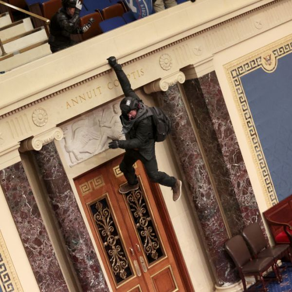 A protester is seen hanging from the balcony in the U.S. Senate Chamber on Jan. 6, 2021. (Win McNamee / Getty Images)