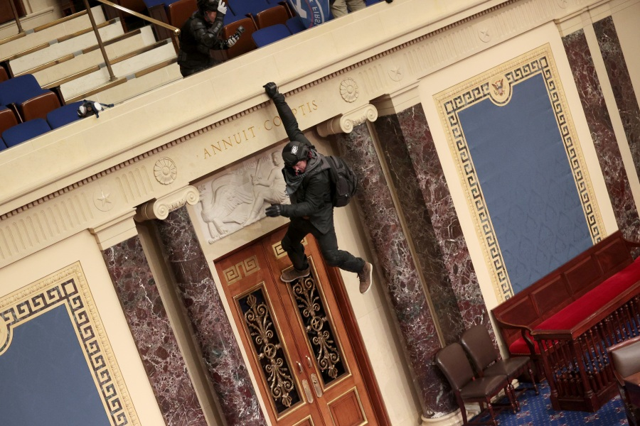 A protester is seen hanging from the balcony in the Senate Chamber on January 06, 2021 in Washington, DC. (Win McNamee/Getty Images)