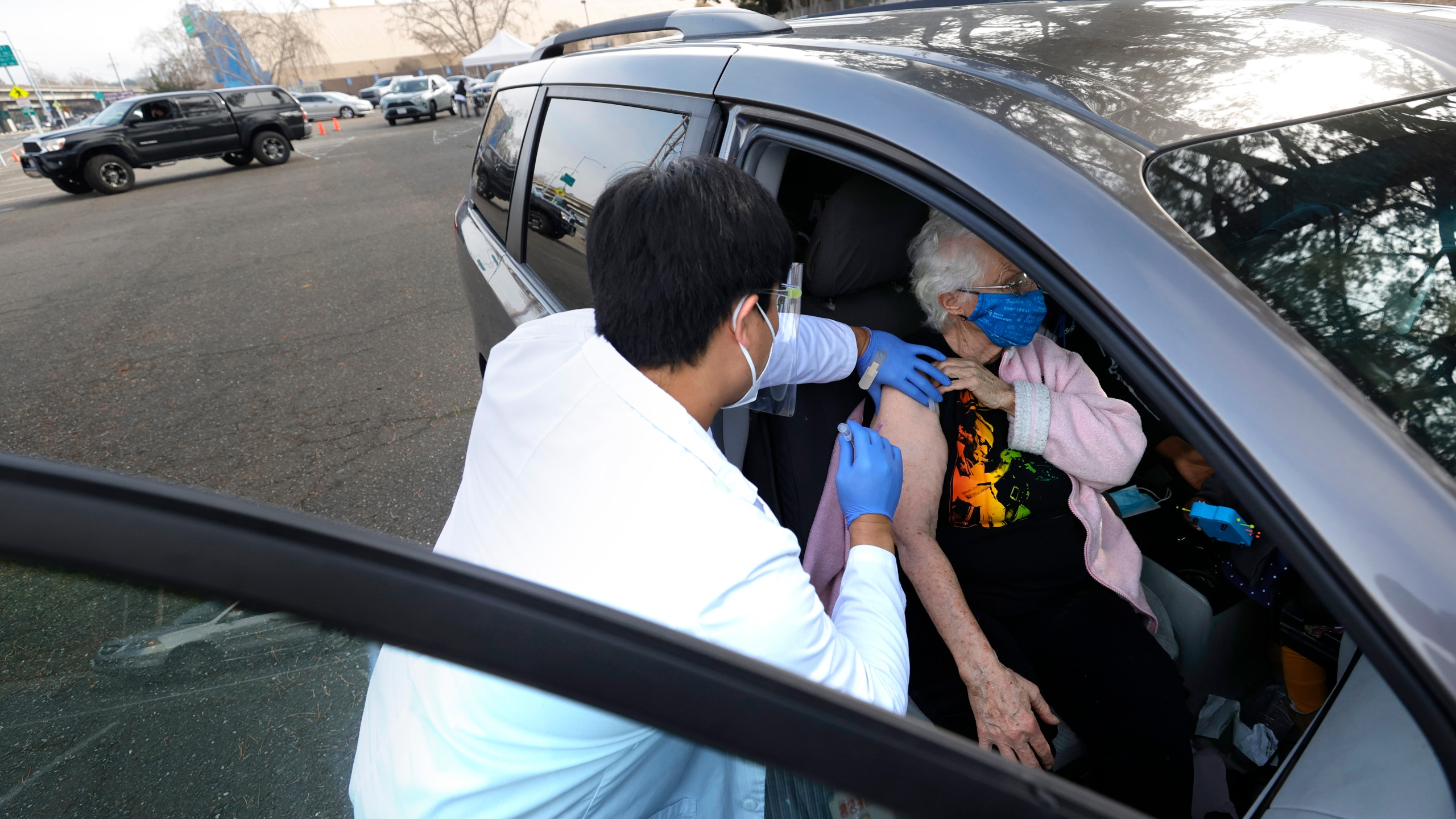 Safeway pharmacist Preston Young (L) administers a Moderna COVID-19 vaccination to Cecile Lusby (R) during a drive-thru vaccination clinic at the Sonoma County Fairgrounds on January 13, 2021 in Santa Rosa, California. (Justin Sullivan/Getty Images)
