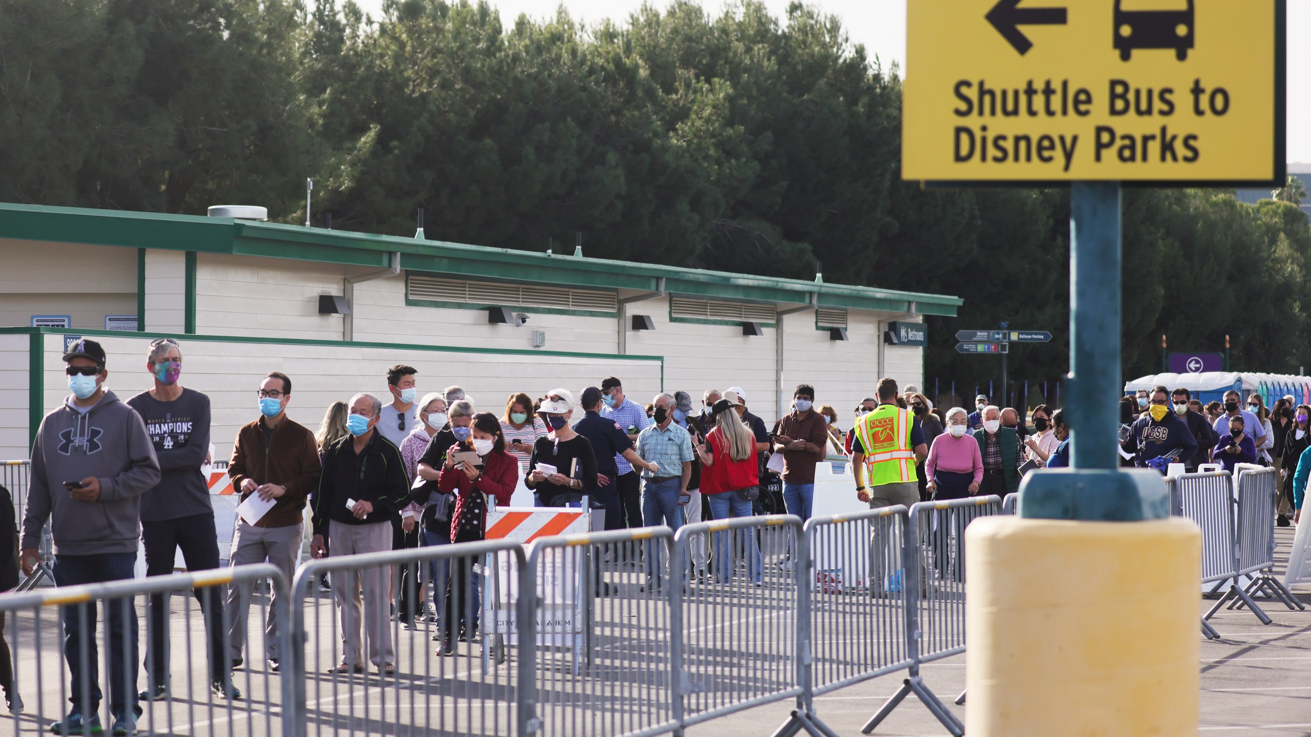 People wait in line to receive the COVID-19 vaccine at a mass vaccination site in a parking lot for Disneyland Resort on January 13, 2021 in Anaheim, California. (Photo by Mario Tama/Getty Images)