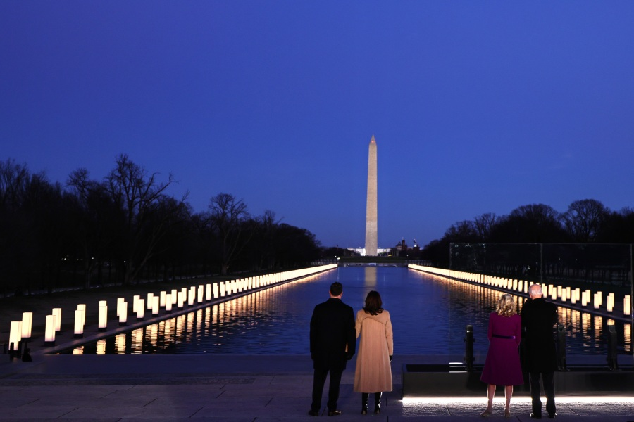 Doug Emhoff, Vice President-elect Kamala Harris, Jill Biden and President-elect Joe Biden face the Reflecting Pool as they observe a moment of silence at a memorial for victims of the coronavirus pandemic at the Lincoln Memorial on the eve of the presidential inauguration on Jan. 19, 2021, in Washington, D.C. (Michael M. Santiago/Getty Images)