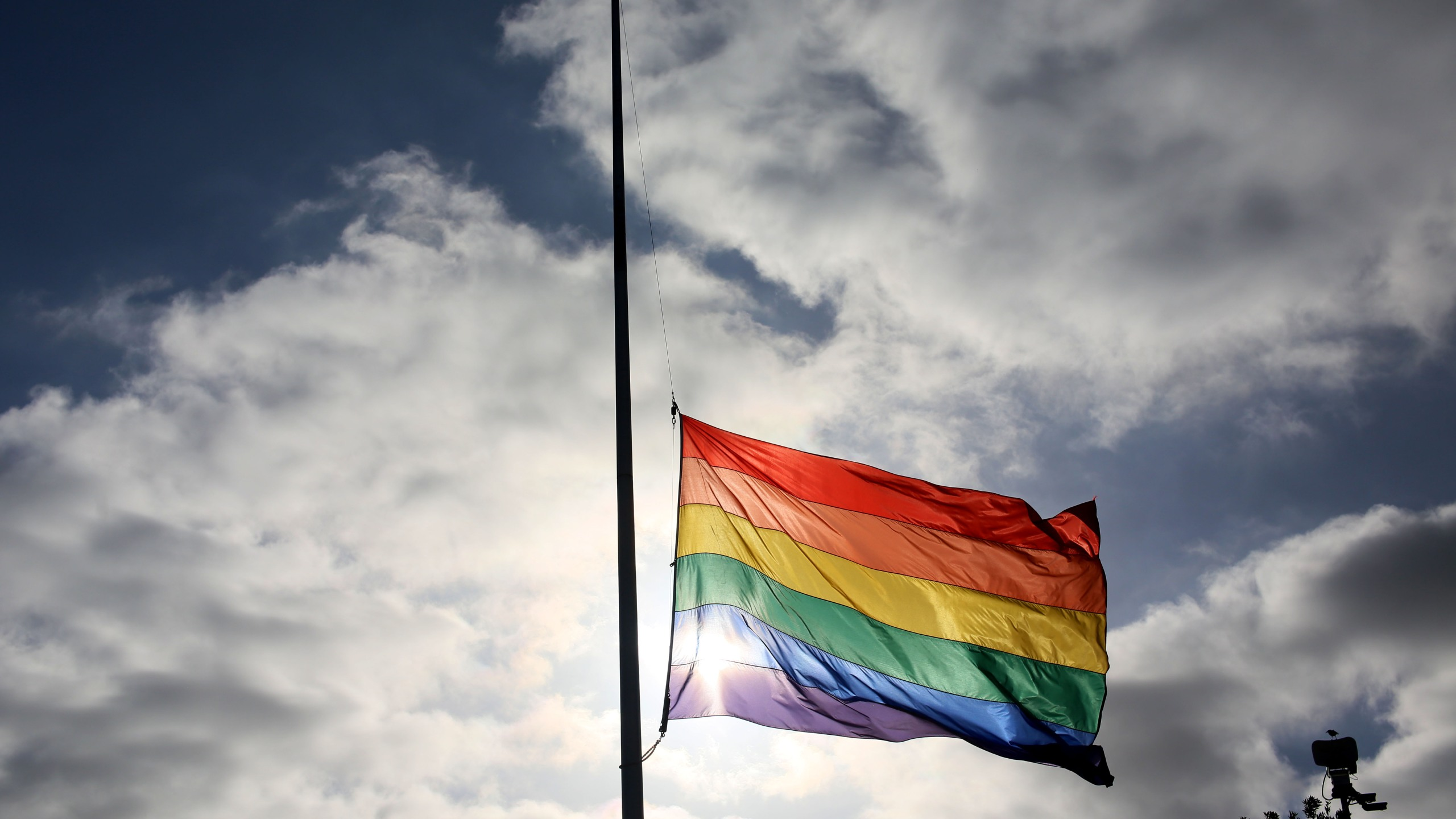 A pride flag stands a half mast during a memorial service in San Diego, California on June 12, 2016, for the victims of the Orlando Nighclub shooting.(Sandy Huffaker/AFP via Getty Images)