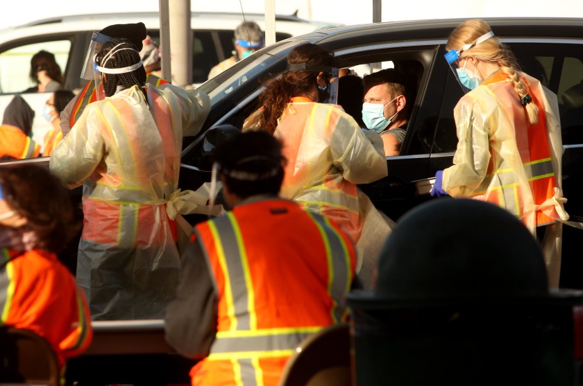 Medical workers tend to people waiting in their cars at a large-scale COVID-19 vaccine site at Cal State Northridge on Tuesday. (Genaro Molina / Los Angeles Times)