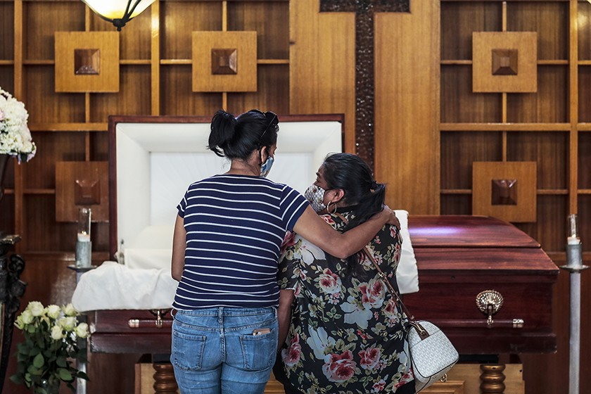 Iris Martinez, right, stands with her friend Grace Salgado before the casket of Martinez's father, Rafael Martinez, who died of COVID-19. (Robert Gauthier / Los Angeles Times)