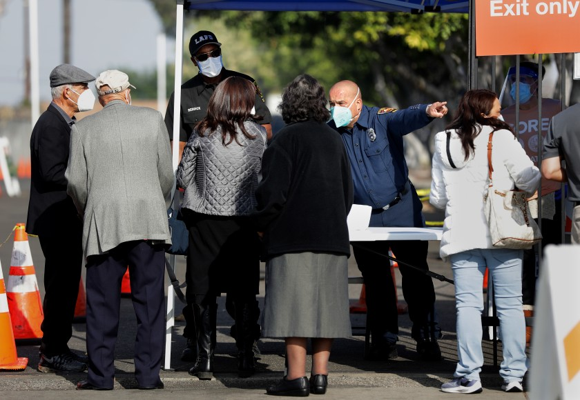 At a checkpoint for a vaccination site in South L.A. on Tuesday, officers from the Los Angeles Fire Department turned away those who did not have an appointment and documentation of a job in the healthcare industry.(Christina House/Los Angeles Times)