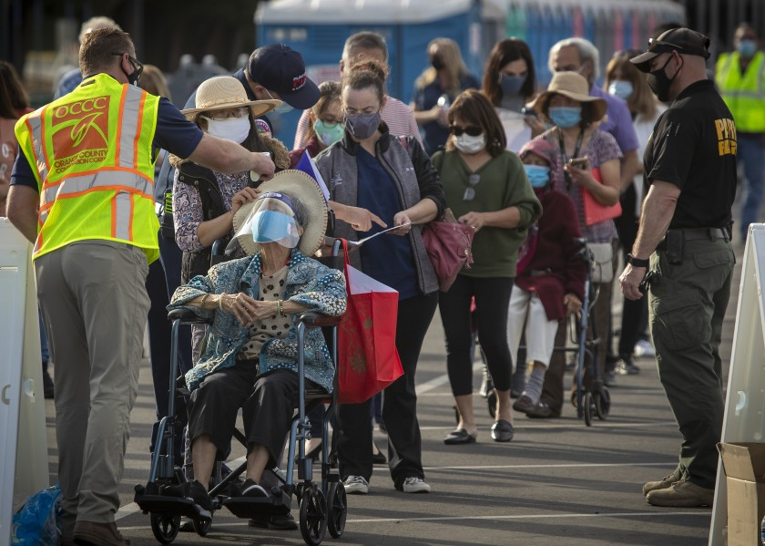 People have their temperatures taken last week at Disneyland, Orange County's first COVID-19 mass vaccination site.(Allen J. Schaben / Los Angeles Times)