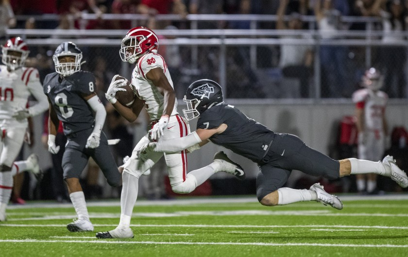 Mater Dei receiver Kody Epps is tacked by St. John Bosco safety Jake Newman during their Trinity League showdown on Oct. 25, 2019.(Allen J. Schaben / Los Angeles Times)