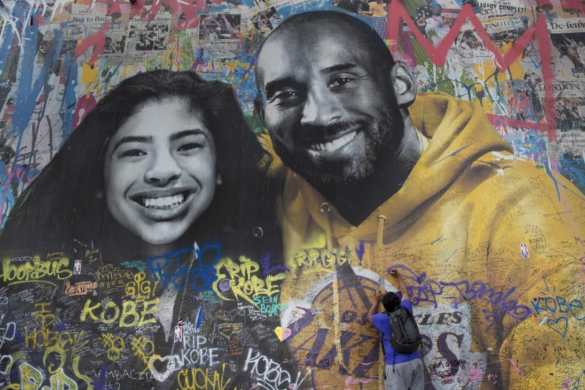A man writes a message on a mural honoring Kobe Bryant and his daughter Gianna in Los Angeles in February 2020. (Mel Melcon / Los Angeles Times)