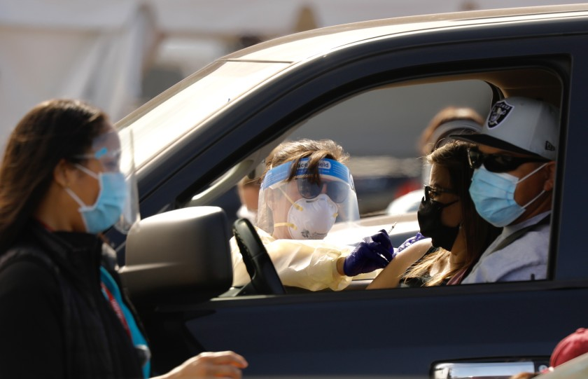 Drivers pull up to a mass vaccination site in the parking lot of the Forum in Inglewood. (Al Seib / Los Angeles Times)