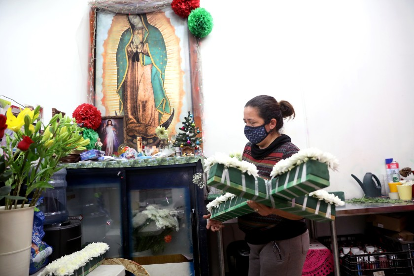 Elizabeth Garibay prepares a floral cross for a funeral at her family business J & I Florist on Dec. 17 in Los Angeles. (Gary Coronado / Los Angeles Times)