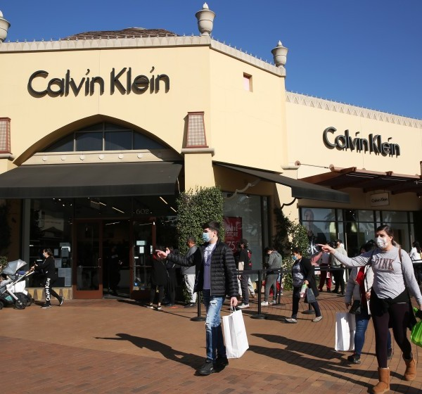 Shoppers wait in line to enter the Calvin Klein store at the Citadel Outlets in Commerce on Dec. 22, 2020. (Dania Maxwell / Los Angeles Times)