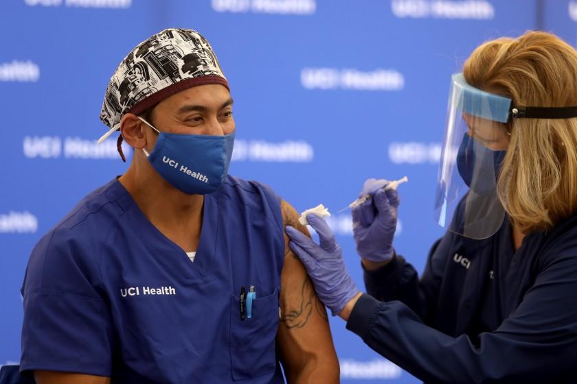Erik Mara, a respiratory therapist at UCI Health, receives a Pfizer BioNTech COVID-19 vaccine on Dec. 16 in Orange. (Gary Coronado / Los Angeles Times)