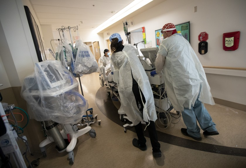 Registered Nurses Cristina Marco, left, and Guillermo Dunne help move a patient last month at the COVID ICU at Providence Holy Cross Medical Center in Mission Hills.(Francine Orr / Los Angeles Times)