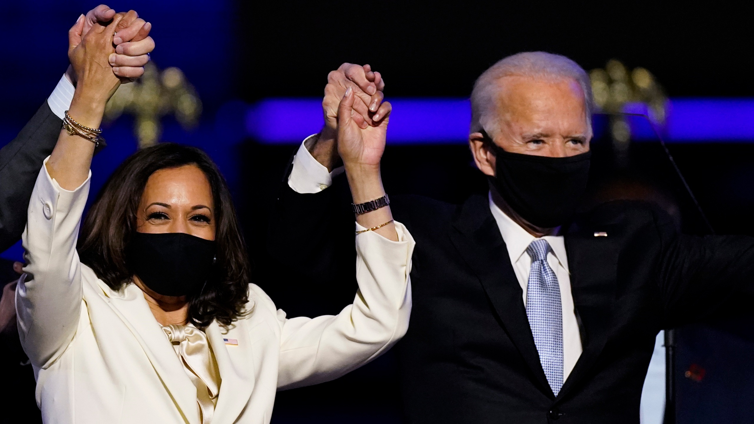 Vice President-elect Kamala Harris holds hands with President-elect Joe Biden and her husband Doug Emhoff as they celebrate Saturday, Nov. 7, 2020, in Wilmington, Del. (AP Photo/Andrew Harnik)