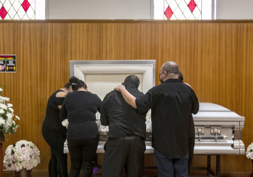 Family members mourn Edith Fernandez alongside her casket Dec. 20 at the Continental Funeral Home in East Los Angeles. The 47-year-old died Dec. 8 from complications of COVID-19.(Brian van der Brug / Los Angeles Times)