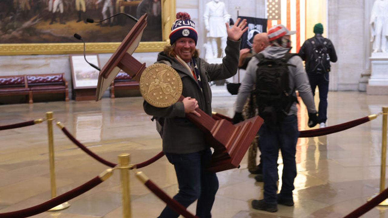 A man, later identified as Adam Johnson of Florida, carries House Speaker Nancy Pelosi's lectern as a mob enters the U.S. Capitol Building on Jan. 6, 2021 in Washington, DC. (Win McNamee/Getty Images)