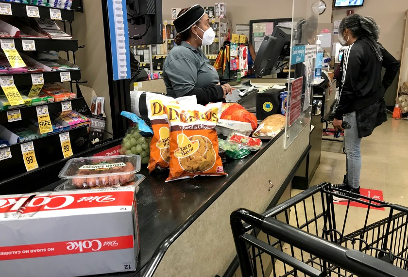 A cashier helps a customer at the checkout stand in the Von's grocery store in Long Beach on Dec. 16, 2020. (Los Angeles Times)